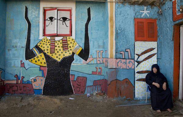 Žena s freskou egyptského malíře Alé Abula Hamada v pozadí v městě Burullus - Sputnik Česká republika