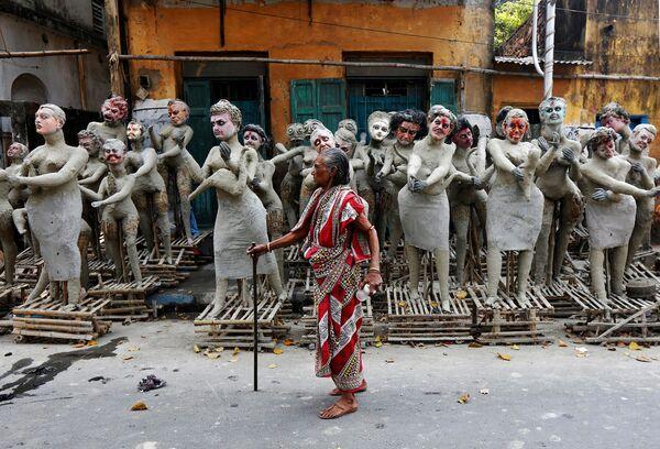 Žena vedle nedokončených hliněných soch hinduistických postav, jež mají být postaveny kolem bohyně Kálí na festivalu Kálí-pudža v Kalkatě - Sputnik Česká republika