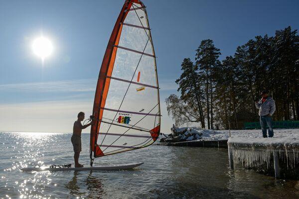 Sportovec Alexandr Orlov surfuje za pětistupňového mrazu na umělém vodojemu Novosibirské vodní elektrárny. - Sputnik Česká republika