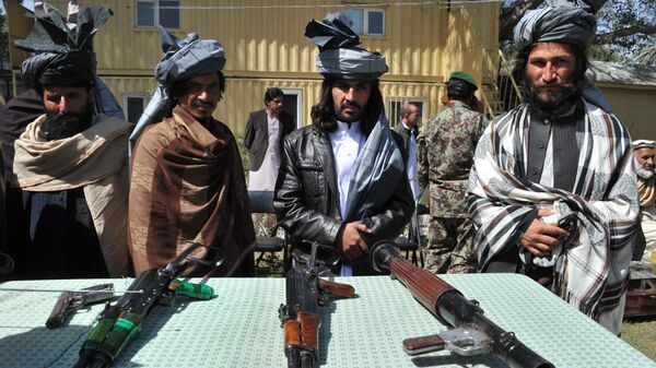 Former Taliban fighters look on as they stand alongside their weapons in Jalalabad, the capital of Nangarhar province on March 19, 2014 - Sputnik Česká republika
