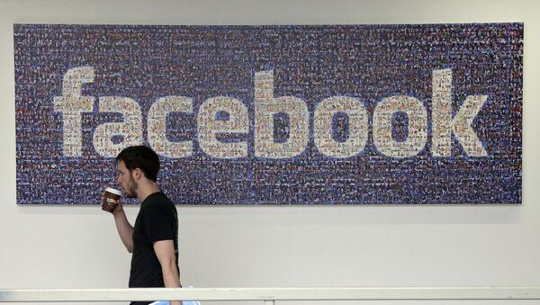 Člověk na pozadí loga Facebooku - Sputnik Česká republika