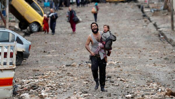 Muž s dcerou v náručí prchá z čtvrti Mosulu ovládané Islámským státem (IS, zakázaná v RF) - Sputnik Česká republika