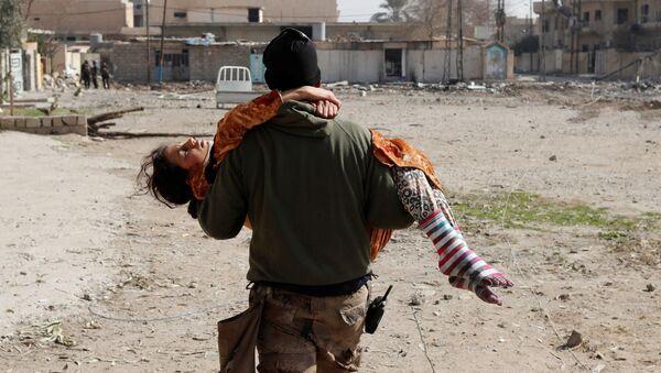Irácký voják nese zraněnou dívku - Sputnik Česká republika