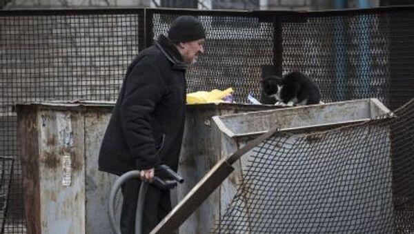 Muž se dívá do odpadkového kontejneru - Sputnik Česká republika