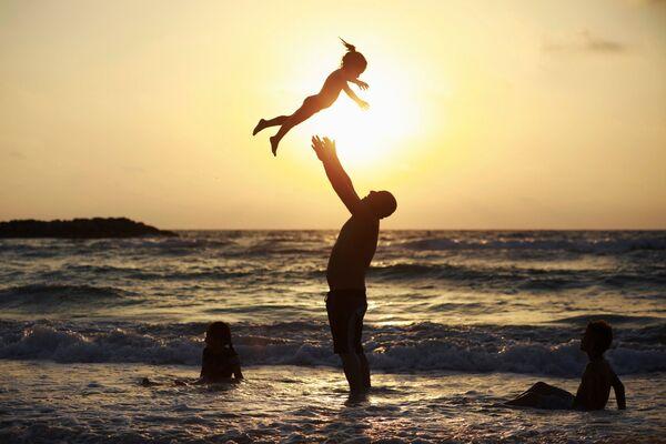 Muž si hraje s dcerou na pláži během oslav Uraza bajramu v Aškelonu, Izrael - Sputnik Česká republika
