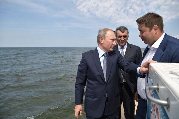 Prezident nejprve vypustil několik rybiček do jezera za pomoci síťky, poté i ostatní tím, že zatáhl za páčku na střeše kontejneru, kde bylo okolo 50 tisíc mláďat - Sputnik Česká republika