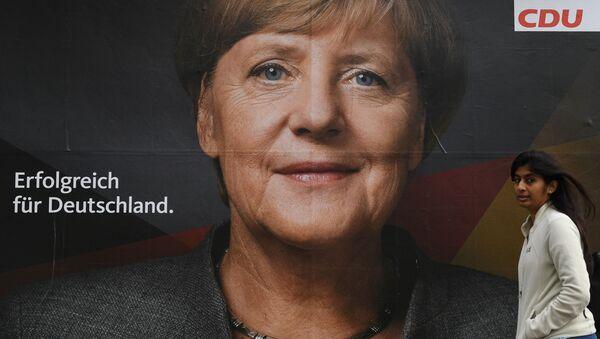 Plakát s vyobrazením německé kancléřky a lídra Křesťanskodemokratické unie Angely Merkelové v jedné berlínské ulici před parlamentními volbami v Německu - Sputnik Česká republika
