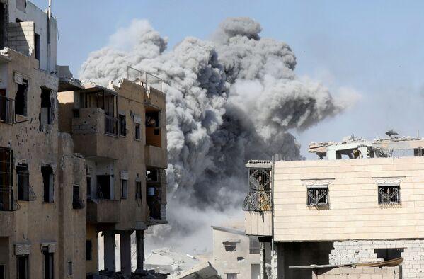 Kouř po leteckém úderu koaličních sil proti teroristům Islámského státu v Rakce, Sýrie - Sputnik Česká republika