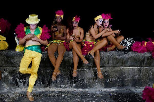 Tanečníci s telefony před začátkem vystoupení na karnevalu v Havaně, Kuba - Sputnik Česká republika