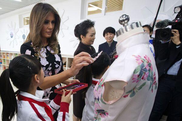 První dáma USA s manželkou Si Ťin pchinga během návštěvy základní školy v Pekingu. - Sputnik Česká republika