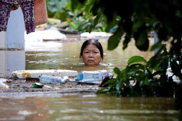 Žena na zaplavené ulici ve vietnamském městě Hội An zařazeném do seznamu UNESCO - Sputnik Česká republika