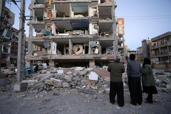 Lidé se dívají na zbořenou budovu po zemětřesení v městě Sere-Pole-Zohab, Írán - Sputnik Česká republika