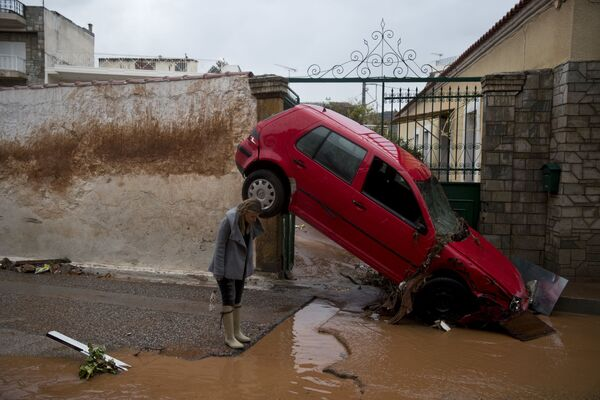 Žena u auta uneseného záplavou v Aténách, Řecko - Sputnik Česká republika