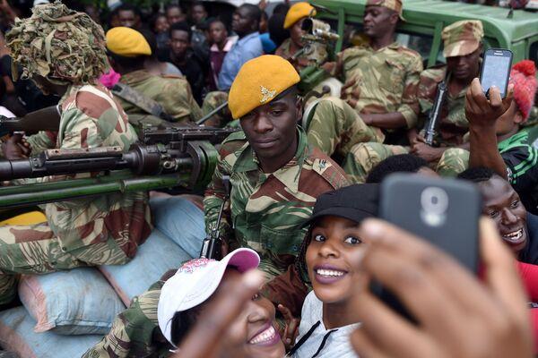Dívky se fotografují s vojákem Zimbabwe během pochodu za odstoupení prezidenta v Harare - Sputnik Česká republika
