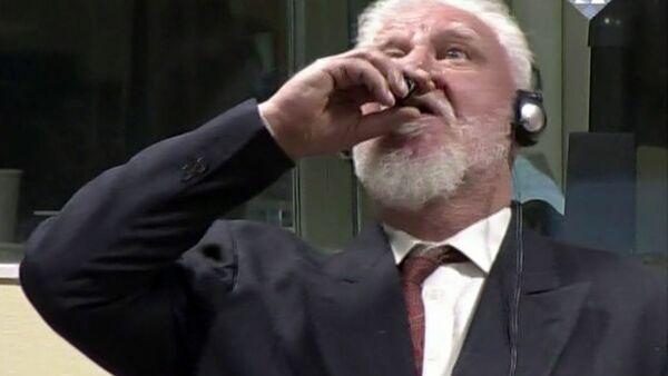 Jeden z vojenských velitelů bosenských Chorvatů, generál Slobodan Praljak, pije jed při zveřejnění odsouzení na zasedání tribunálu v Haagu - Sputnik Česká republika