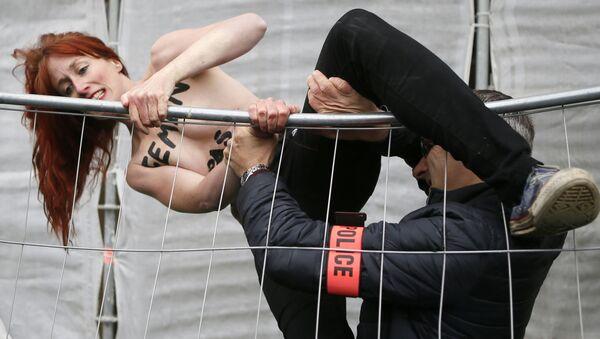 Aktivistka hnutí FEMEN se snaží přelézt plot během akce proti Marine Le Penové na severu Francie. - Sputnik Česká republika