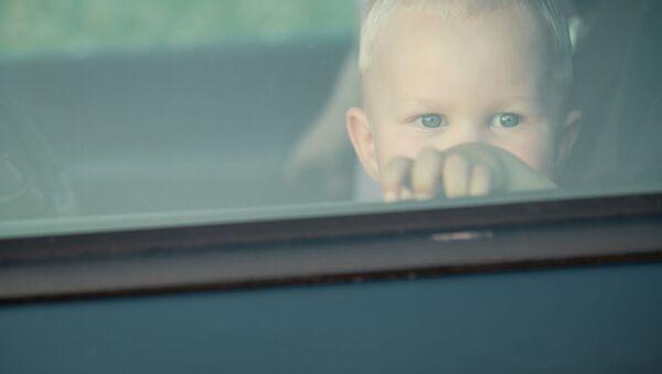 Malé dítě se dívá přes okno automobilu - Sputnik Česká republika