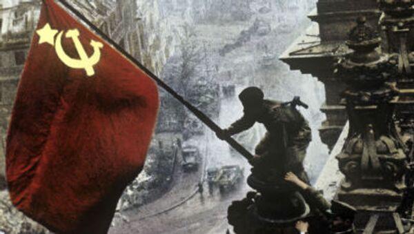 Sovětský voják vztyčuje rudou vlajku nad Reichstagem dne 1. května 1945. - Sputnik Česká republika