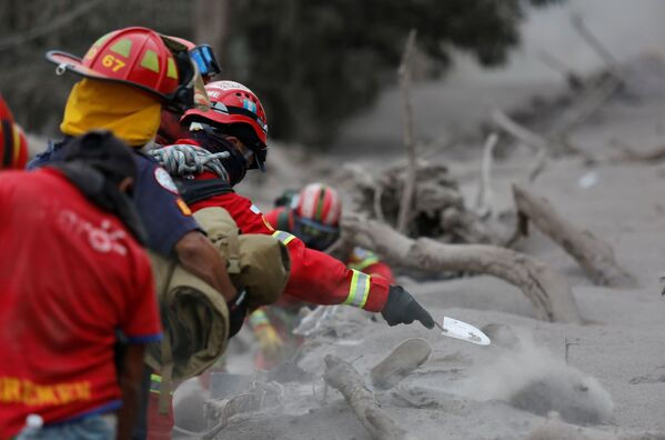 Záchranáři vykopávají popel po erupci sopky Fuego v Guatemale - Sputnik Česká republika