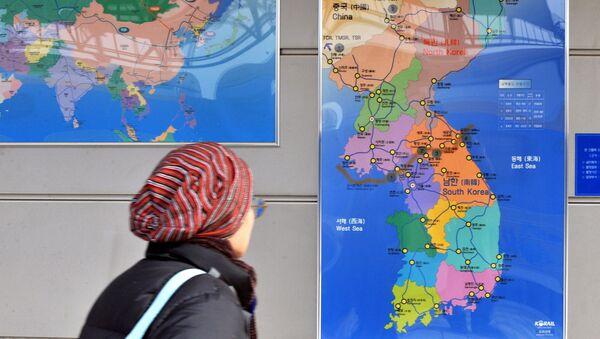 Cestující na nádraží se dívá na mapu Korejského poloostrova - Sputnik Česká republika