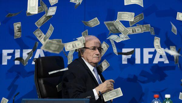 Prezident FIFA Sepp Blatter se dívá na falešné dolary, které házeli protestující během tiskové konference v sidle v Curychu. - Sputnik Česká republika