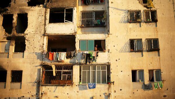 Palestinci se dívají z domu, který byl poškozen před rokem během izraelského ostřelování ve městě Bajt Lahíja, Pásmo Gazy. - Sputnik Česká republika