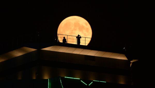 Měsíc během zatmění na pozadí mrakodrapu Groznyj City v Čečně - Sputnik Česká republika
