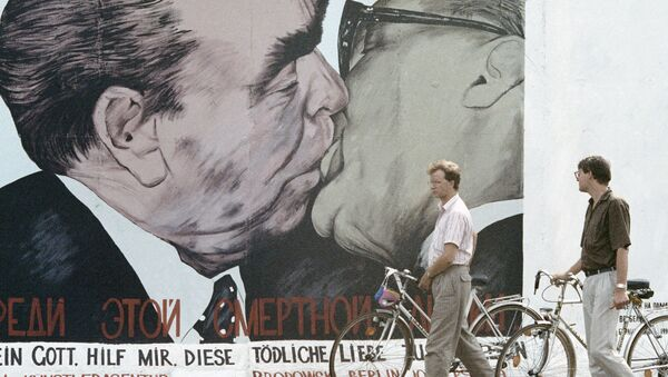 Жители Берлина рассматривают оставленный не разрушенным участок берлинской стены, расписанный художником - Sputnik Česká republika
