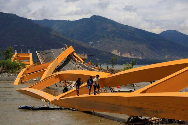 Lidé procházející se po zdevastovaném mostě, který zničilo zemětřesení a tsunami (Sulawesi, Indonésie). - Sputnik Česká republika