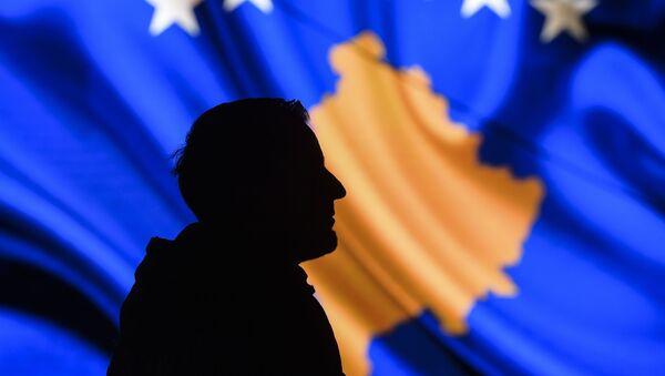Muž na pozadí vlajky Kosova. - Sputnik Česká republika