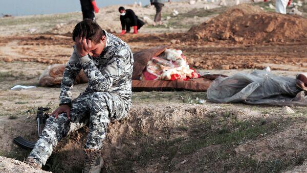 Irácký policista na místě hromadného pohřebiště na území, které se nacházelo pod kontrolou teroristické skupiny Islámský stát* - Sputnik Česká republika