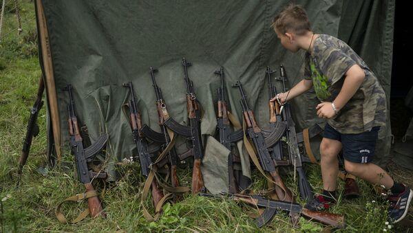 Kluk vedle útočných pušek AK-47 ve vojensky organizovaném kempu u Ternopilu - Sputnik Česká republika