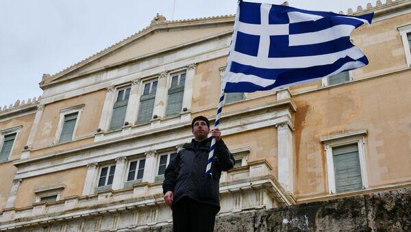 Účastník protestní akce v budově řeckého parlamentu drží vlajku Řecka.  - Sputnik Česká republika