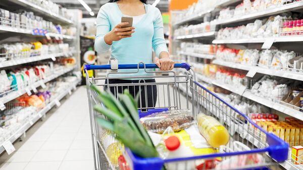 Dívka s nákupním vozíkem v obchodě. Ilustrační foto - Sputnik Česká republika