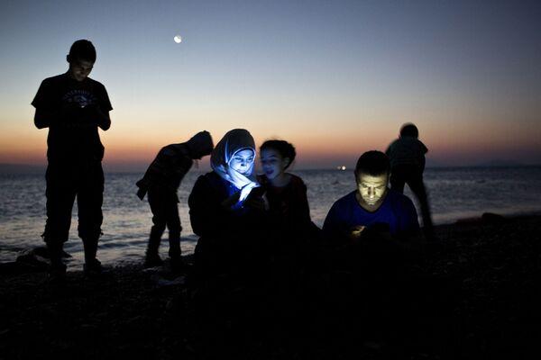 Migranti prověřují svoje mobilní telefony po východu na souši z nafukovacího člunu na řeckém ostrově Kos - Sputnik Česká republika