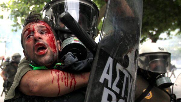 Demonstranta zadržuje policie během protestů proti úsporným opatřením. - Sputnik Česká republika