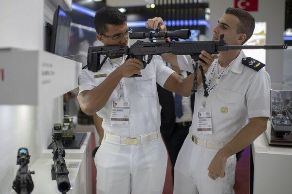 Vojenští námořníci kontrolují střelnou zbraň na Mezinárodním veletrhu obrany a bezpečnosti LAAD 2019 v Rio de Janeiru, Brazílie - Sputnik Česká republika