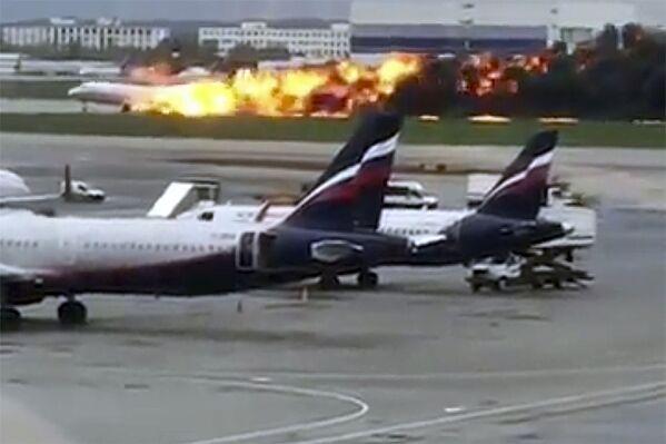 Na snímku z videa, poskytnutého uživatelem Instagramu @artempetrovich, letadlo SSJ-100 společnosti Aeroflot hoří během nouzového přistání na letišti Šeremetěvo v Moskvě v Rusku v neděli 5. května 2019 - Sputnik Česká republika