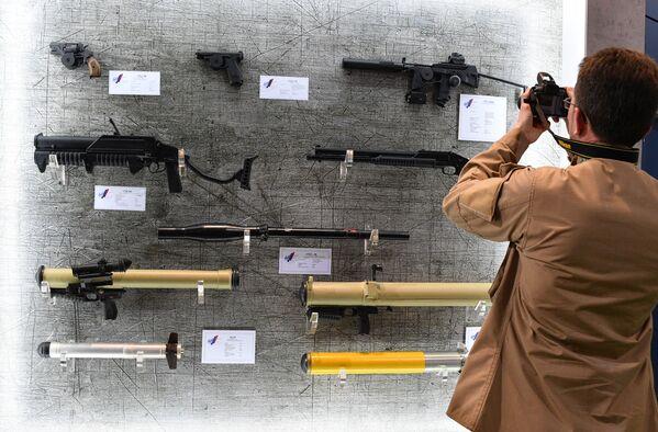 Návštěvník výstavy MILEX-2019 fotí stánek se zbraněmi - Sputnik Česká republika
